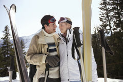 在温暖的衣物的愉快的滑雪夫妇有滑雪的 图库摄影
