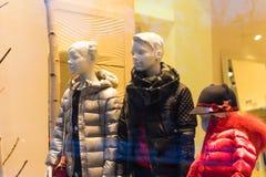 在温暖的衣裳的儿童时装模特在商店窗口里 库存图片