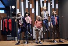 在温暖的衣裳的儿童时装模特在商店windowow 销售额 免版税图库摄影