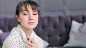 在温暖的被编织的格子花呢披肩包裹的特写镜头画象害羞浪漫妇女享用在客厅 股票视频