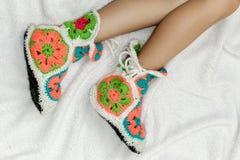 在温暖的被编织的袜子的被晒黑的女性腿在轻的背景 免版税库存照片