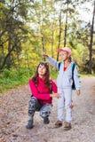 在温暖的晴朗的秋天天照顾走与她的孩子 库存图片