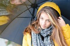在温暖的黄色外套的美丽的妇女伞 免版税库存图片