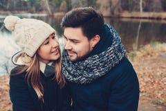 在温暖被编织的帽子和围巾走的愉快的夫妇室外在秋天森林里 免版税库存图片