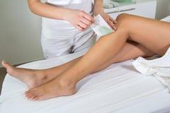 在温泉打蜡的妇女腿 免版税库存图片