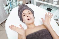 在温泉沙龙的害怕的年轻深色的妇女等待的温泉治疗 整容术 库存照片