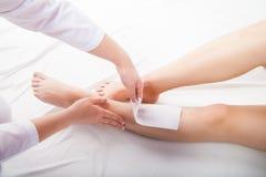给在温泉沙龙的美容师妇女腿打蜡 图库摄影