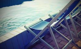 在温泉的水池边缘的空的轻便折叠躺椅没有人的 库存图片