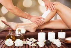 给在温泉的男性美容师妇女的腿打蜡 免版税图库摄影