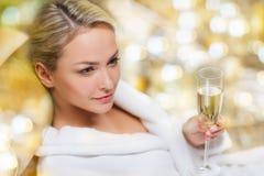 在温泉的美丽的少妇饮用的香槟 免版税库存照片