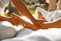在温泉的身体按摩 关闭按摩女性腿的手 库存照片