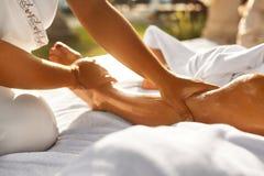 在温泉的身体按摩 关闭按摩女性腿的手 库存图片