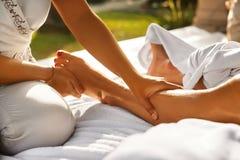 在温泉的身体按摩 关闭按摩女性腿的手 免版税库存图片