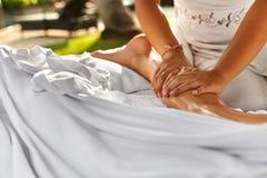 在温泉的身体按摩 关闭按摩女性腿的手 免版税库存照片