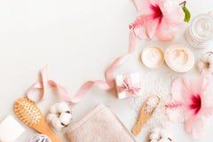 在温泉的顶视图设置了与一朵自然肥皂、奶油、毛巾和木槿花在白色木背景与拷贝空间 免版税库存图片