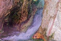 在温泉附近的小瀑布在主要,有铁、铜、锰和硫化合物色的沉淀物的  免版税库存照片