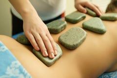 在温泉,在治疗师手上的焦点的石按摩 库存图片