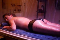 在温泉治疗期间的说谎的轻松的妇女。颜色疗法。 库存照片