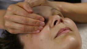 在温泉saton的塑料面孔按摩 妇女享受一个专业按摩治疗师慢动作的服务 股票视频
