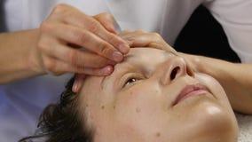 在温泉saton的塑料面孔按摩 妇女享受一位专业按摩治疗师4K的服务 影视素材