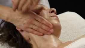 在温泉saton的塑料面孔按摩 妇女享受一位专业按摩治疗师4K的服务 股票录像