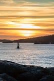 在港口口岸海岸日落航行蟒蛇上的橙色和黄色天空 免版税库存照片