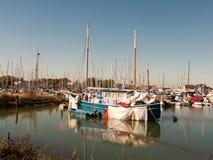 在港口小游艇船坞场面帆柱前面的停放的私有小船 免版税库存图片