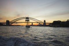 在港口桥梁附近的高船在日落 库存图片
