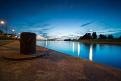 在港口码头的系船柱在微明期间有在江边的一个看法 免版税库存照片