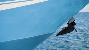 在港港口的一艘蓝色船有与船锚的海背景 免版税库存图片