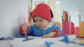在游戏室温暖地打扮的一个小孩子画在册页的铅笔 股票录像