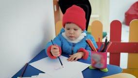 在游戏室温暖地打扮的一个小孩子画在册页的铅笔 股票视频