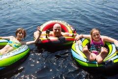 在游泳在湖的可膨胀的管的乐趣 免版税库存图片
