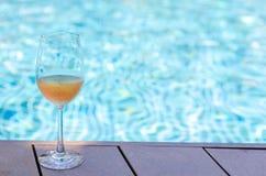 在游泳场上玫瑰酒红色把放的一杯 免版税库存照片