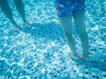 在游泳场下的两条男孩的腿-假日概念 图库摄影
