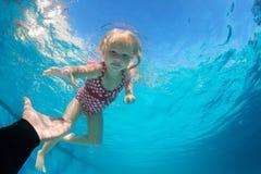 在游泳场到达延长的手的在水面下儿童下潜 免版税图库摄影