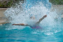 在游泳场的水滑道乐趣在撞入水的夏天做大飞溅 免版税库存照片