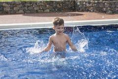 在游泳场的男孩plaiyng 免版税库存照片