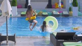 在游泳场的苗条快乐的女孩乐趣,公司到有在行跑的可膨胀的圆环的泳装里和跃迁入 影视素材