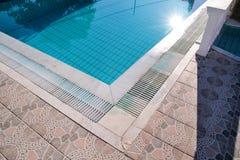 在游泳场的蓝色被剥去的水与路面边缘的热带手段的  一部分的游泳场底下背景 免版税库存照片
