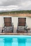 在游泳池和湖之间的二把椅子山的 免版税图库摄影