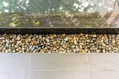 在游泳池天沟的小卵石  图库摄影