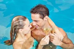 在游泳池敬酒的夫妇 库存照片