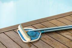 在游泳池旁边的刷子和叶子漏杓 免版税库存图片