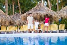 在游泳池旁边的年轻家庭在热带手段 库存图片