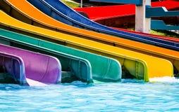 在游泳池的五颜六色的塑料水滑道 免版税图库摄影