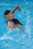 在游泳池的亚洲孩子游泳-与力量反撞力的爬泳样式 库存照片