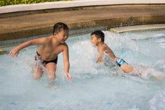 在游泳池的亚洲男孩微笑 免版税库存照片