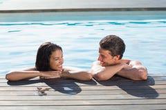 在游泳池的夫妇在一个晴天 免版税库存照片