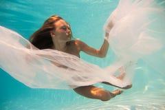 在游泳池的妇女undewater 免版税库存图片